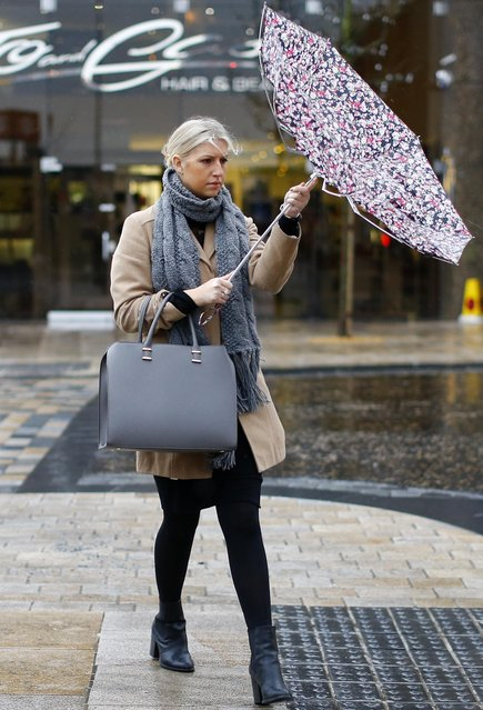A woman struggles with her umbrella during windy weather in Preston, northern England January 28, 2015. (Photo by Darren Staples/Reuters)