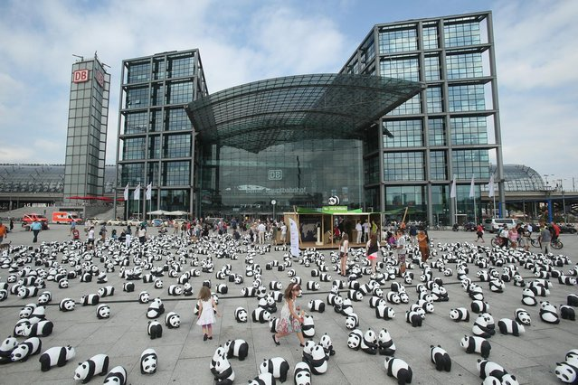 Elaia (C), 6, and her sister Lusitta, 4, play among 1,600 styrofoam panda bear sculptures displayed in front of Hauptbahnhof main railway station by the World Wildlife Fund on August 5, 2013 in Berlin, Germany. The WWF is celebrating its 50th anniversary and is drawing attention to the fact that only 1,600 panda bears remain in the wild. The display will soon travel to 25 other cities in Germny. (Photo by Sean Gallup/Getty Images)