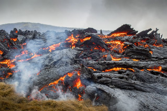 Lava flows from the erupting Fagradalsfjall volcano some 40 km west of the Icelandic capital Reykjavik, on March 21, 2021. Weekend hikers took the opportunity Sunday to inspect the area where a volcano erupted in Iceland on March 19, some 40 kilometres (25 miles) from the capital Reykjavik, the Icelandic Meteorological Office said, as a red cloud lit up the night sky and a no-fly zone was established in the area. (Photo by Marco Di Marco/AP Photo)