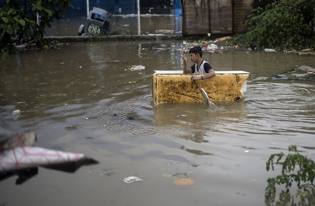 A man paddles a makeshift boat made of insulation from a refrigerator through a flooded street due to continuous rains caused by tropical depression Josie in Marikina, east of Manila on July 22, 2018. (Photo by Noel Celis/AFP Photo)