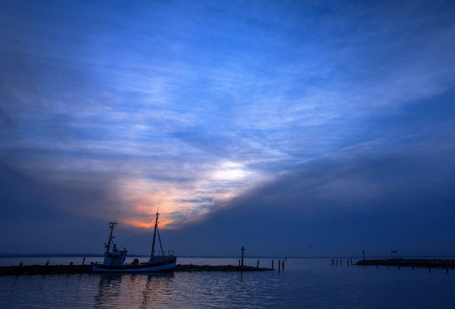 A fishing boat anchors at the small fishing harbor of Timmendorf during sunset on the island of Poel in the Baltic Sea, Germany, Monday, January 19, 2015. (Photo by Jens Buettner/AP Photo/DPA)