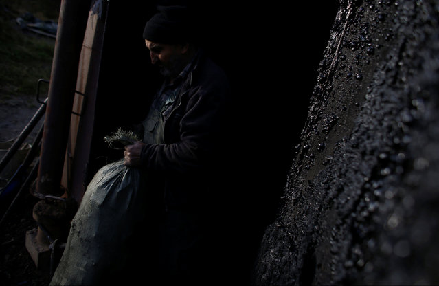 Charcoal burner Zygmunt Furdygiel holds sack of charcoal at a charcoal making site in the forest of Bieszczady Mountains, near Baligrod village, Poland November 5, 2016. (Photo by Kacper Pempel/Reuters)