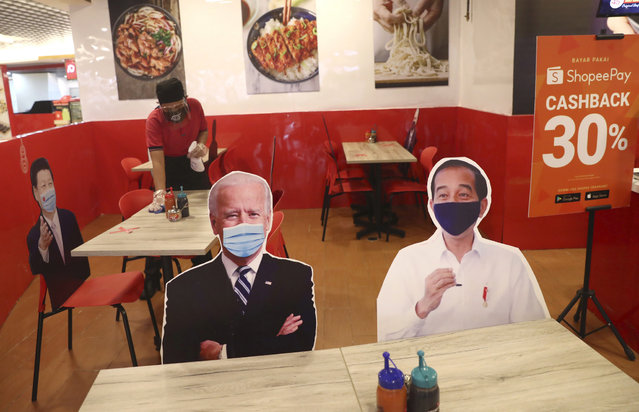 An employee cleans a table at a noodle restaurant that uses cardboard cutouts of U.S. President Joe Biden, Indonesian President Joko Widodo and other world leaders as physical distancing markers amid concerns of the spread of coronavirus outbreak, at a shopping mall in Jakarta, Indonesia, Tuesday, March 9, 2021. (Photo by Tatan Syuflana/AP Photo)