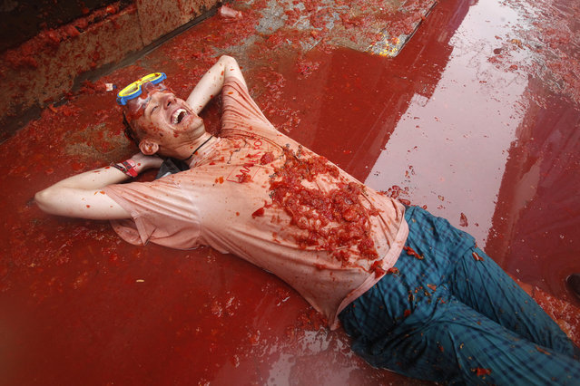 """A man lays on a puddle of tomato during the annual """"tomatina"""" tomato fight fiesta in the village of Bunol, 50 kilometers outside Valencia, Spain, Wednesday, August 28, 2013. Thousands of people are splattering each other with tons of tomatoes in the annual """"Tomatina"""" battle in recession-hit Spain, with the debt-burdened town charging participants entry fees this year for the first time. Bunol town says some 20,000 people are taking part in Wednesday's hour-long street bash, inspired by a food fight among kids back in 1945. Participants were this year charged some 10 euros ($13) to foot the cost of the festival. Residents do not pay. (Photo by Alberto Saiz/AP Photo)"""