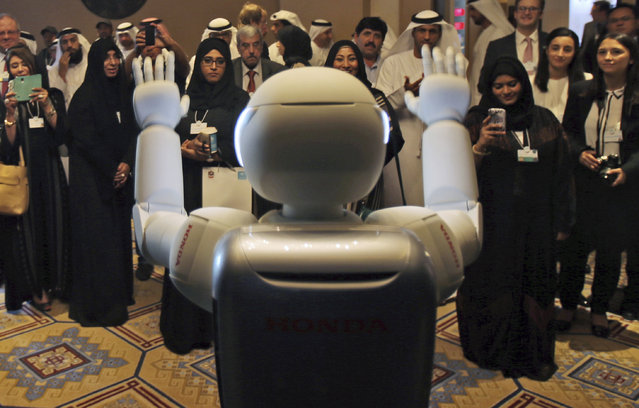A humanoid robot designed and developed by Honda and named Asimo waves for the audience at the end of the company's presentation during the last day of the Government Summit in Dubai, United Arab Emirates, Wednesday, February 11, 2015. (Photo by Kamran Jebreili/AP Photo)