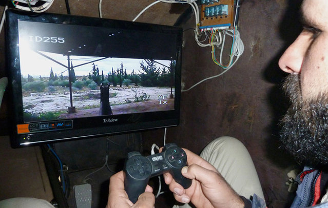 A Syrian rebel uses a videogame controller to activate the machine gun of Sham 2, a homemade armored vehicle made by the rebels' Al-Ansar brigade, in Bishqatin, 4 km west of Aleppo, on December 8, 2012. (Photo by Herve Bar/AFP Photo)