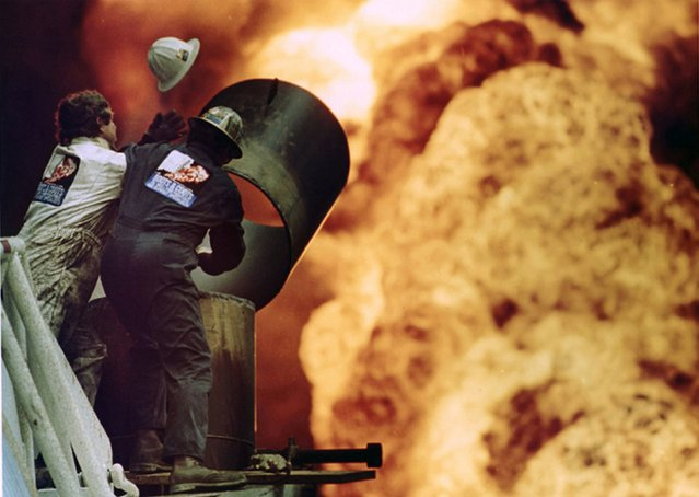 Oil fire fighters from Boots and Coots try to put out an oil well fire in Al-Ahmadi where retreating Saddam Hussein forces had set fire to the oil wells, in this March 30, 1991 file photo. Russell Boyce: The workers were trying to contain the flames with a shield and tube when a blast of heat blew off the helmet of one of the workers. (Photo by Russell Boyce/Reuters)