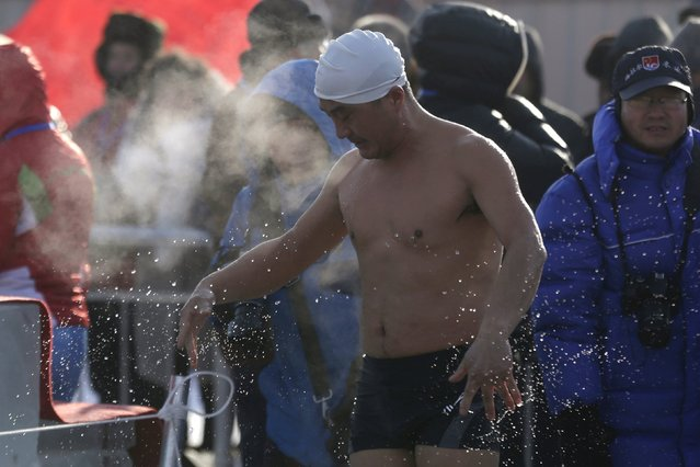 A swimmer shakes water off after finishing the competition in a pool carved from thick ice covering the Songhua River during the Harbin Ice Swimming Competition in the northern city of Harbin, Heilongjiang province, January 5, 2016. (Photo by Aly Song/Reuters)