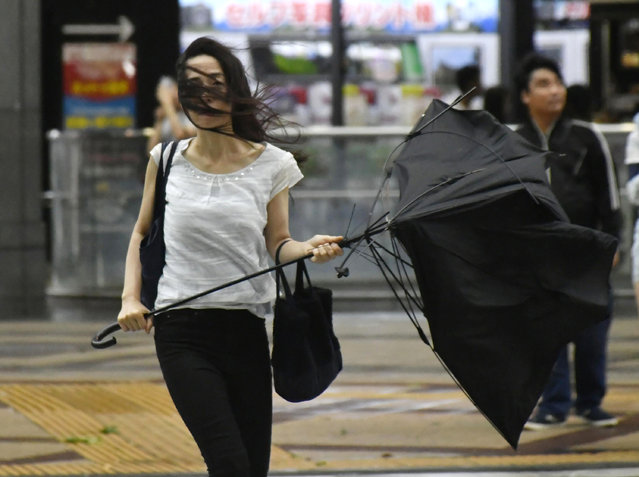 A woman holds broken umbrella as a powerful typhoon hits Osaka, western Japan, Tuesday, September 4, 2018. A powerful typhoon blew through western Japan on Tuesday, causing heavy rain to flood the region's main offshore international airport and high winds to blow a tanker into a connecting bridge, disrupting land and air travel. (Photo by Nobuki Ito/Kyodo News via AP Photo)