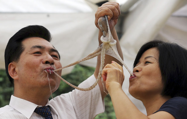 A South Korean couple eats a live octopus during an event to promote a local food festival in Seoul, South Korea, Thursday, Sept. 12, 2013. Live octopus is delicacy in the country. (Photo by Shin Jun-hee/AP Photo/Yonhap)