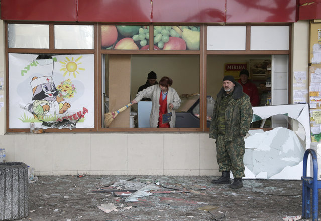 A woman cleans shattered glass after a shop was damaged when a bus station was hit during the recent shelling between Russian-backed separatists and Ukrainian government forces in Donetsk, Ukraine, Wednesday, February 11, 2015. (Photo by Petr David Josek/AP Photo)