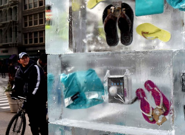 People pass by leisure items frozen in a giant block of ice during a JetBlue Airways event in Madison Square Park January 7, 2016 in New York. The event was to promote JetBlue Airways seasonal nonstop service between New York City and Palm Springs this winter. (Photo by Timothy A. Clary/AFP Photo)
