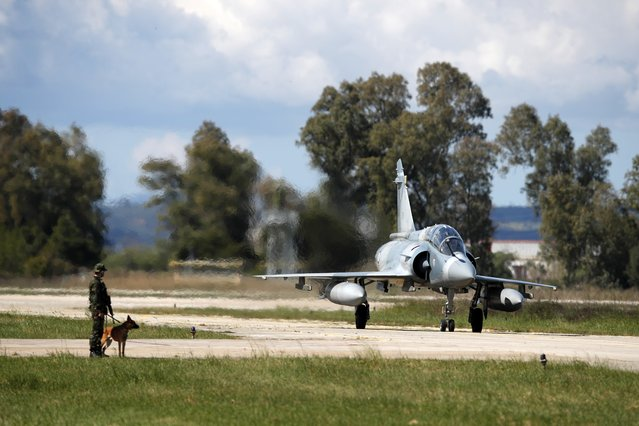 A Greek crew of a Mirage 2000-5 taxis as a soldier with a dog guards at Andravida air base, about 279 kilometres (174 miles) southwest of Athens, Tuesday, April 20, 2021. Greece vowed Tuesday to expand military cooperation with traditional NATO allies as well as Middle Eastern powers in a race to modernize its armed forces and face its militarily assertive neighbor Turkey. (Photo by Thanassis Stavrakis/AP Photo)