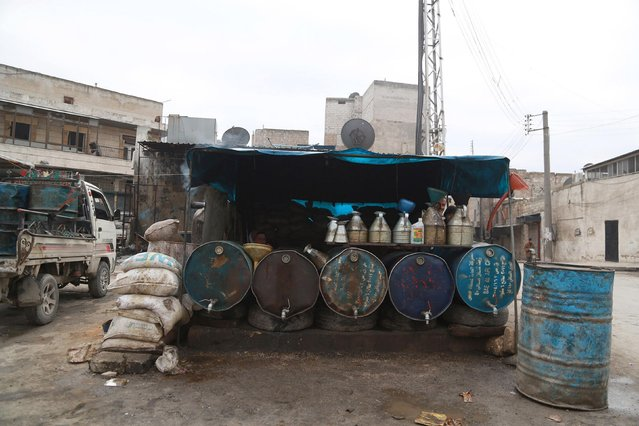 Fuel vendors rest behind fuel barrels in Aleppo January 13, 2015. (Photo by Nour Kelze/Reuters)