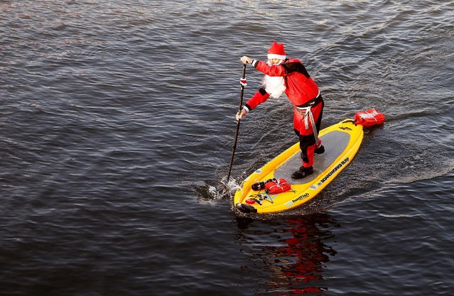 A man dressed as  a Santa Claus (Samichlaus) crosses the Limmat river on his stand-up paddle in Zurich, Switzerland December 4, 2016. (Photo by Arnd Wiegmann/Reuters)