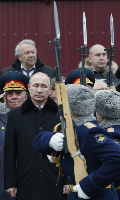 Russian President Vladimir Putin (L) watches honor guards passing by as he attends a wreath laying ceremony to mark the Defender of the Fatherland Day at the Tomb of the Unknown Soldier by the Kremlin walls in central Moscow February 23, 2015. (Photo by Sergei Karpukhin/Reuters)