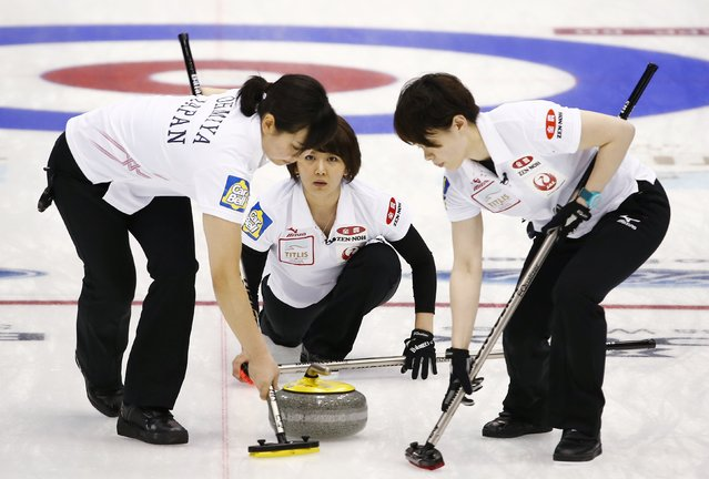 Japan's third Sayaka Yoshimura (C) delivers a stone as her team mates Anna Ohmiya (L) and Kaho Onodera sweep during their curling round robin game against Scotland at the World Women's Curling Championships in Sapporo March 15, 2015. (Photo by Thomas Peter/Reuters)