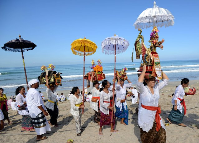 Balinese people carry offerings during the Melasti ceremony prayer at Kuta beach on the island of Bali on March 18, 2015. (Photo by Sonny Tumbelaka/AFP Photo)
