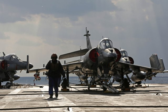 A  crew members walks on the flight deck past Super Etendard fighter jets aboard France's Charles de Gaulle aircraft carrier on missino in the Gulf, January 29, 2016. (Photo by Philippe Wojazer/Reuters)