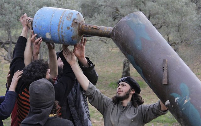 Rebel fighters from Suqour al-Sham Brigade prepare a locally made shell before launching it towards forces loyal to Syria's president Bashar Al-Assad in Idlib countryside March 18, 2015. (Photo by Mohamad Bayoush/Reuters)