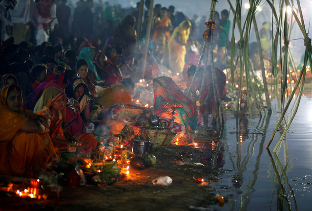 Hindu devotees prepare to worship the Sun god on the banks of the Sabarmati river during the religious festival of Chhath Puja in Ahmedabad, India, November 14, 2018. (Photo by Amit Dave/Reuters)