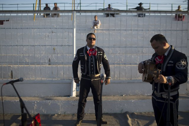 Mariachi singer Jordani Reyes, 28 (C), relaxes before performing at the International Livestock Fair Show in Havana March 16, 2015. (Photo by Alexandre Meneghini/Reuters)