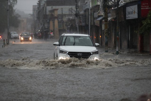 A car moves through a flooded street during monsoon rains Jammu, India, Monday, July 12, 2021. India's monsoon season runs from June to September. (Photo by Channi Anand/AP Photo)