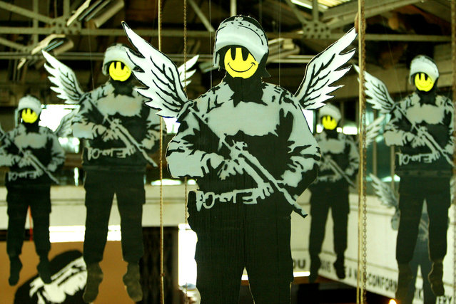 Cartoon images of policemen with wings and smiley faces are seen during a Banksy exhibition in London in 2003. (Photo by Reuters/Stringer)