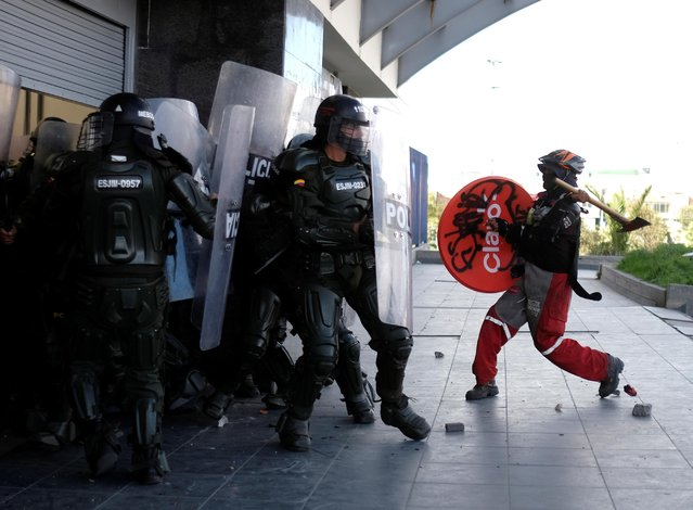 A demonstrator raises an axe towards riot police during anti-government protests, as Colombia commemorates Independence Day, in Bogota on July 20, 2021. (Photo by Santiago Mesa/Reuters)