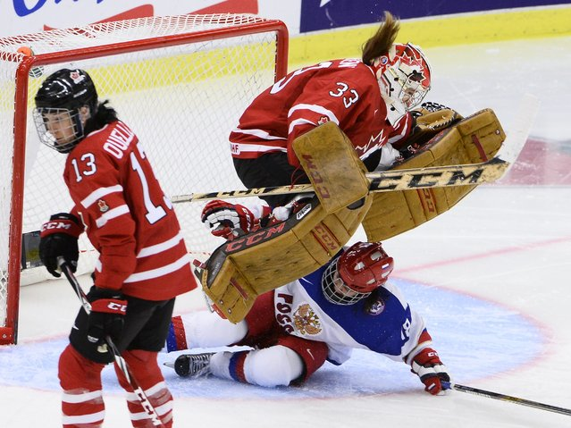 Canada's goalkeeper Ann-Renee Desbiens (33) jumps over Russia's Olga Sosina as Canadian Caroline Ouellette looks away during the 2015 IIHF Ice Hockey Women's World Championship group A match between Canada and Russia at Malmo Isstadion in Malmo, southern Sweden, Sunday, March 29, 2015. (Photo by Claudio Bresciani/AP Photo/TT)