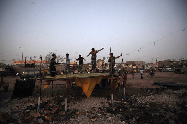 Children play on a trampoline in open ground during dusk in Karachi's slum February 19, 2015. (Photo by Akhtar Soomro/Reuters)