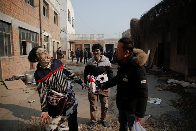 Actors rehearse their roles during the filming of the post-apocalyptic movie Zombie Era at an abandoned factory complex in Langfang, Hebei province, China December 16, 2016. (Photo by Damir Sagolj/Reuters)