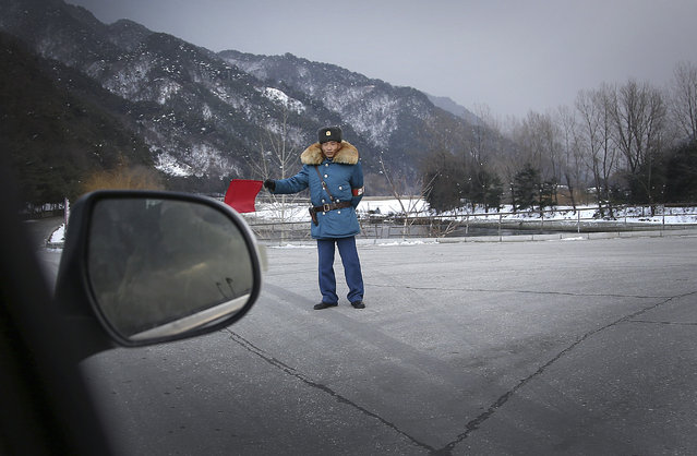 A North Korean traffic police officer directs traffic in a road intersection Thursday, December 3, 2015, in Hyangsan county, North Pyongan, North Korea. (Photo by Wong Maye-E/AP Photo)