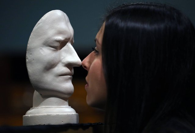 Sir Isaac Newton's death mask held by staff member Emma Smith is part of an exhibition of 150 fascinating items from Edinburgh University's collection displayed at it's main library in Edinburgh, on December 4, 2013. (Photo by David Cheskin/PA Wire)