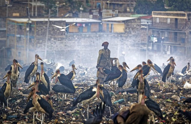 In this photo taken Wednesday, December 5, 2018, a woman who scavenges recyclable materials from garbage for a living is seen through a cloud of smoke from burning trash, surrounded by Marabou storks who feed on the garbage, at the dump in the Dandora slum of Nairobi, Kenya. As the world meets again to tackle the growing threat of climate change, how the continent tackles the growing solid waste produced by its more than 1.2 billion residents, many of them eager consumers in growing economies, is a major question in the fight against climate change. (Photo by Ben Curtis/AP Photo)