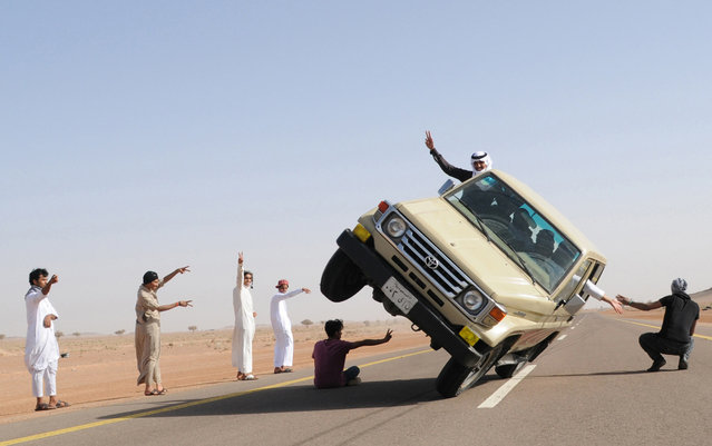 """Saudi youths demonstrate a stunt known as """"sidewall skiing"""" (driving on two wheels) in the northern city of Hail, in Saudi Arabia March 30, 2013. Performing stunts such as sidewall skiing and drifts is a popular hobby amongst Saudi youths. (Photo by Reuters)"""
