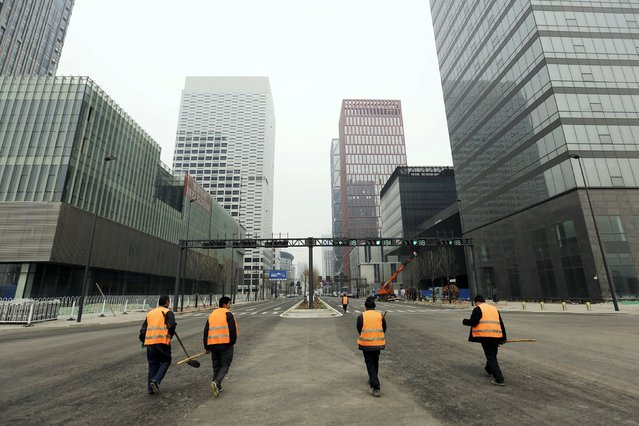 Workers walk through the Yujiapu financial centre, in Tianjin, China February 22, 2016. Yujiapu, part of a highly touted financial district in Tianjin's Binhai New Area once billed by leaders as China's answer to Manhattan, has drawn scrutiny from experts as an example of the costly infrastructure splurges that fuelled development across the country at the height of the economic boom. (Photo by Jason Lee/Reuters)
