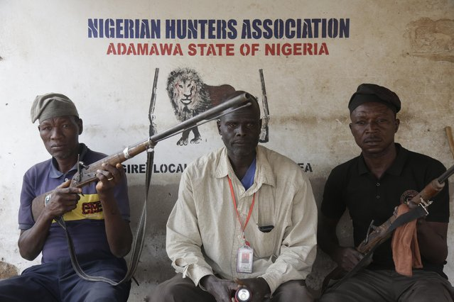 Local hunters pose with dane guns near a polling station following the presidential election being delayed by the Independent National Electoral Commission in Yola, Nigeria, Saturday, February 16, 2019. (Photo by Sunday Alamba/AP Photo)