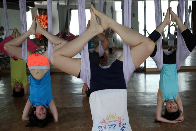 Some women doing yoga pose using the hammocks during the Anti-Gravity yoga class at Svarga e-Motion Sanctuary at Dharmawangsa Square, Jakarta, Saturday, April 18, 2015. (Photo by Jurnasyanto Sukarno/JG Photo)