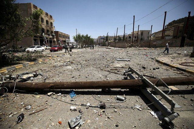 A fallen electricity column is seen at a damaged street, caused by an April 20 air strike that hit a nearby army weapons depot, in Sanaa April 21, 2015. (Photo by Mohamed al-Sayaghi/Reuters)