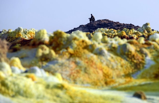 An Ethiopian soldier looks on from a hilltop next to a sulphur lake in the Danakil Depression on January 23, 2017 near Dallol, Ethiopia. (Photo by Carl Court/Getty Images)