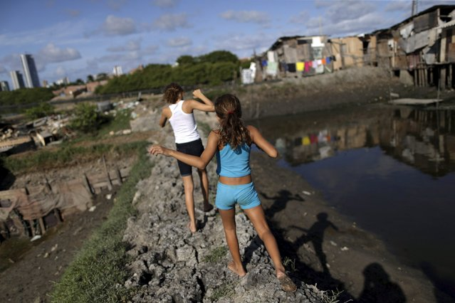"Children walk in front of stilt houses at a lake dwelling also known as palafitte or ""Palafito"" in Recife, Brazil, March 1, 2016. (Photo by Ueslei Marcelino/Reuters)"