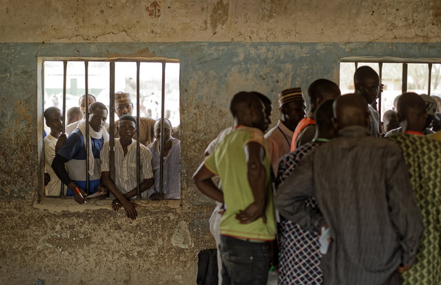 People peer through a window as party agents huddle together to watch votes being counted inside a polling station in Kano, northern Nigeria Saturday, Februaary 23, 2019. Nigerians went to the polls for a presidential election Saturday, one week after a surprise delay for Africa's largest democracy. (Photo by Ben Curtis/AP Photo)