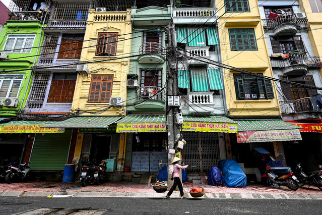 """This photograph taken on June 8, 2021 shows a street vendor walking past narrow residential houses, known as """"nha ong"""" in Vietnamese or """"tube houses"""", in an urban area of Hanoi. (Photo by Manan Vatsyayana/AFP Photo)"""