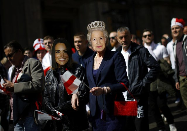 Women wearing masks depicting Britain's Queen Elizabeth and Catherine, Duchess of Cambridge take part in a Saint George's Day parade in Nottingham, central England, April 23, 2015. (Photo by Darren Staples/Reuters)