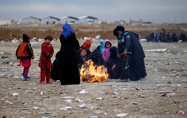 Displaced Iraqis gather near a fire to warm up after fleeing the battle between Iraqi rapid response forces and Islamic State militants near Mosul, Iraq, January 25, 2017. (Photo by Ahmed Jadallah/Reuters)