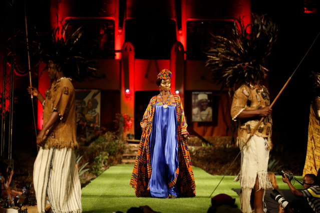 "A model walks on a catwalk during a fashion show featuring African fashion and culture as part of a gala marking the launch of a book called ""African Twilight: The Vanishing Rituals and Ceremonies of the African Continent"" at the African Heritage House in Nairobi, Kenya on March 3, 2019. (Photo by Baz Ratner/Reuters)"