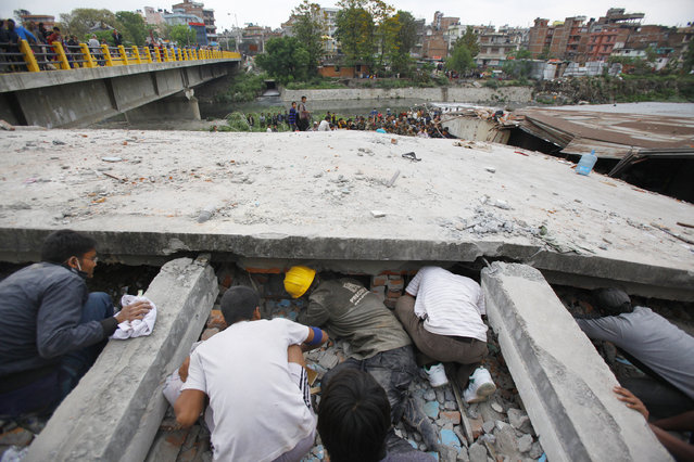 Rescuers look for victims under a building that collapsed after an earthquake  in Kathmandu, Nepal, Saturday, April 25, 2015. (Photo by Niranjan Shrestha/AP Photo)