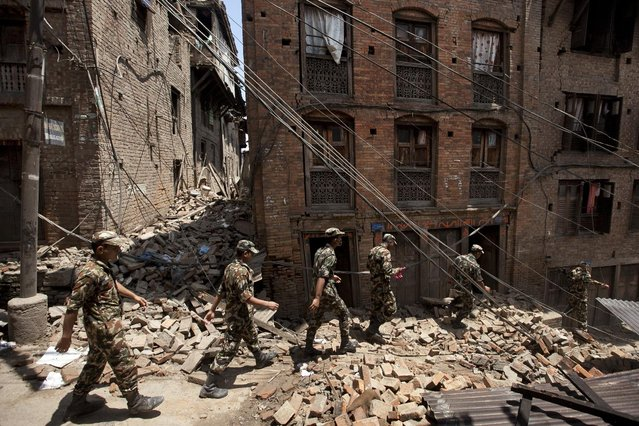 Members of the Nepalese army walk through a damaged area caused by Saturday's earthquake, in Bhaktapur, on the outskirts of Kathmandu, Nepal, Monday, April 27, 2015. (Photo by Niranjan Shrestha/AP Photo)