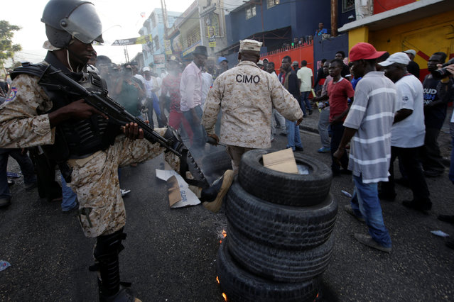A police officer kicks a tire barricade made by protesters during a demonstration against the results of the presidential election in Port-au-Prince, Haiti, December 16, 2016. (Photo by Andres Martinez Casares/Reuters)